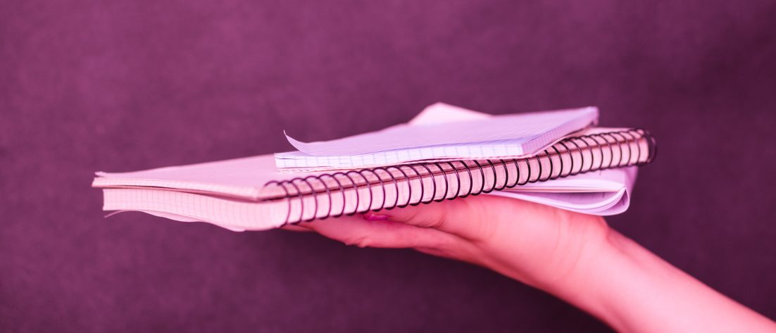 Hand holding a notebook and papers