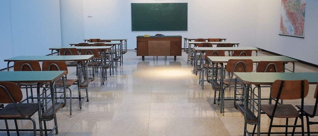empty classroom with desks and a chalkboard