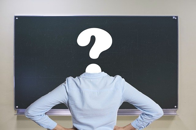 teacher facing a blackboard with question mark where her head should be