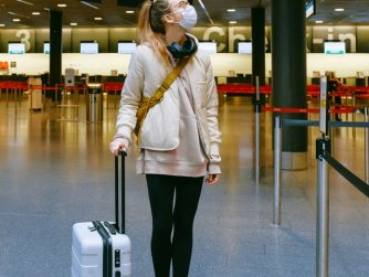Girl wearing a mask and pulling a suitcase in an airport