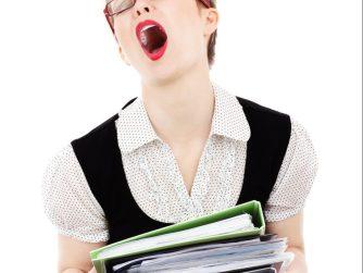 Woman yawning carrying books
