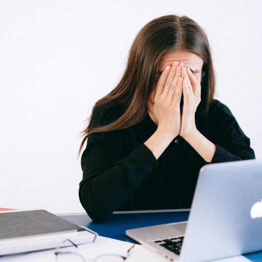 Woman covering face sitting in front of a computer